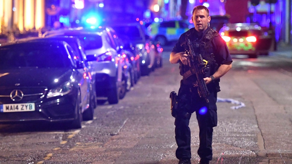 An armed police stands on Borough High Street as police are dealing with an incident on London Bridge in London, Saturday, June 3, 2017. Witnesses reported a vehicle hitting pedestrians and injured people on the ground. (Dominic Lipinski / PA via AP)
