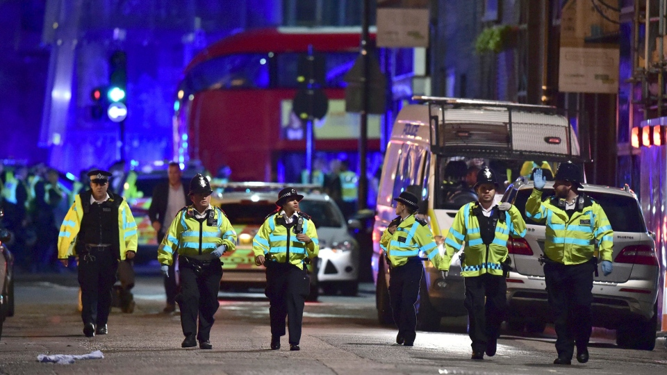 Police officers on Borough High Street as police are dealing with an incident on London Bridge in London, Saturday, June 3, 2017. Witnesses reported a vehicle hitting pedestrians and injured people on the ground. (Dominic Lipinski / PA via AP)