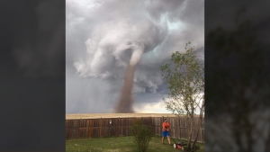 Theunis Wessels is shown mowing his lawn while a tornado descends in Three Hills, Alta., on June 2, 2017. (Cecilia Wessels / Facebook)