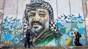 Palestinians walk by a section of the Israeli separation barrier with a graffiti depicting the late Palestinian leader Yasser Arafat, while on their way to attend the first Friday prayers in Jerusalem's al-Aqsa mosque during Muslim holy month of Ramadan, at the Qalandia Israeli army checkpoint, between the West Bank city of Ramallah and Jerusalem, on Friday, June 2, 2017. (AP Photo/Nasser Nasser)