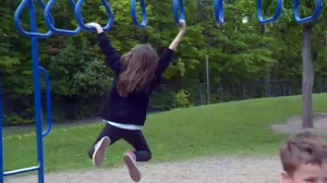 A girl swings on monkey bars at a school in Ste. Foy, Quebec on June 5, 2017