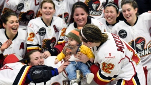 Calder Reid, son of coach Scott Reid and player Meaghan Mikkelson-Reid (12, right) gets placed in the Clarkson Cup trophy after their win over Les Canadiennes de Montreal in Canadian Women's Hockey League final action, Sunday March 13, 2016, in Ottawa. (Justin Tang/The Canadian Press)