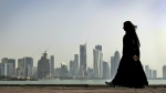A Qatari woman walks in front of the city skyline in Doha, Qatar on May 14, 2010. (AP / Kamran Jebreili)