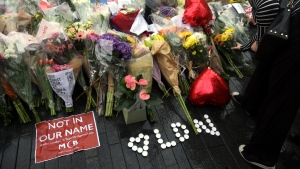 People look at the floral tributes after a vigil for victims of Saturday's attack in London Bridge, at Potter's Field Park in London, Monday, June 5, 2017. (AP Photo / Tim Ireland)