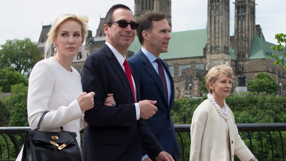 Minister of Finance Bill Morneau, second right, and his wife Nancy McCain walk with U.S. Treasury Secretary Steven Mnuchin, centre left, and Louise Linton through a park in Ottawa, June 9, 2017. (Adrian Wyld / THE CANADIAN PRESS)