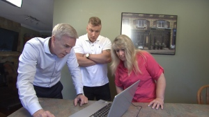 Ross McLaughlin looks at a binary trading website with Shelley and Spencer Meyer. (CTV)