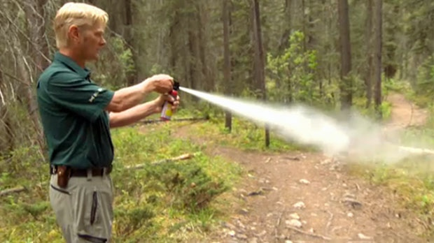 Jon Stuart-Smith demonstrates the proper way to deploy bear spray on a trail off the Bow Valley Parkway in Banff National Park