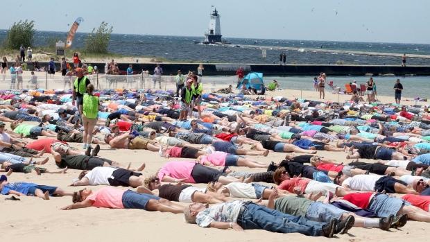 People take part in an attempt to break the Guinness Book record for simultaneous sand angels on Saturday, June 10, 2017 in Ludinton, Mich. (Jeff Kiessel/Ludington Daily News via AP)