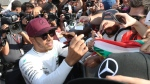 Mercedes driver Lewis Hamilton (44) of Great Britain signs autographs after winning the Canadian Grand Prix Sunday, June 11, 2017 in Montreal. (Paul Chiasson / THE CANADIAN PRESS)