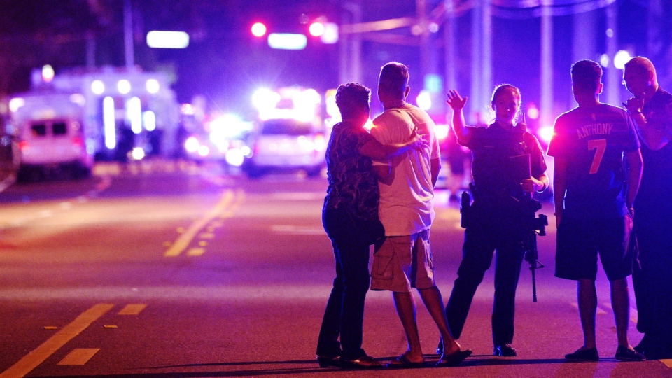 An Orlando Police officers direct family members away from a fatal shooting at Pulse nightclub in Orlando, Fla. on June 12, 2016. (AP / Phelan M. Ebenhack)