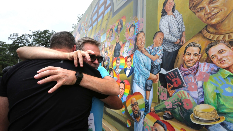 Artist Yuriy Karabash hugs a family member of a victim at the Pulse nightclub, on June 12, 2017. (Joe Burbank /Orlando Sentinel via AP)