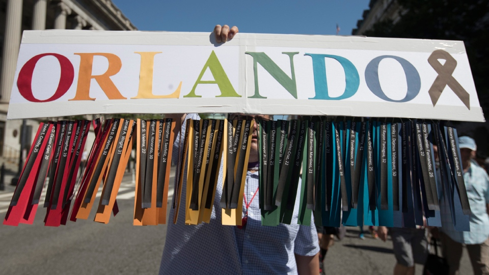 Gil Mendez holds a sign to honour the victims of the shooting at the Pulse Nightclub in Orlando, Fla. (Carolyn Kaster / AP)