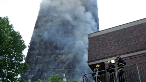 Firefighters in place as they battle a massive fire that raged in a high-rise apartment building in London, Wednesday, June 14, 2017. (AP Photo/Matt Dunham)
