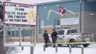 Members of the RCMP stand outside the La Loche Community School in La Loche, Sask. Monday, Jan. 25, 2016. (Jonathan Hayward/The Canadian Press)