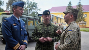 In this file photo, Canadian and Ukrainian servicemen talk during the opening ceremony of a joint military exercises in Lviv, Ukraine, Monday, Sept. 14, 2015. (THE CANADIAN PRESS / AP / Pavlo Palamarchuk)