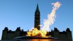 The Centre Block of the Parliament Buildings is shown through the Centennial Flame on Parliament Hill in Ottawa.  (THE CANADIAN PRESS / Fred Chartrand)
