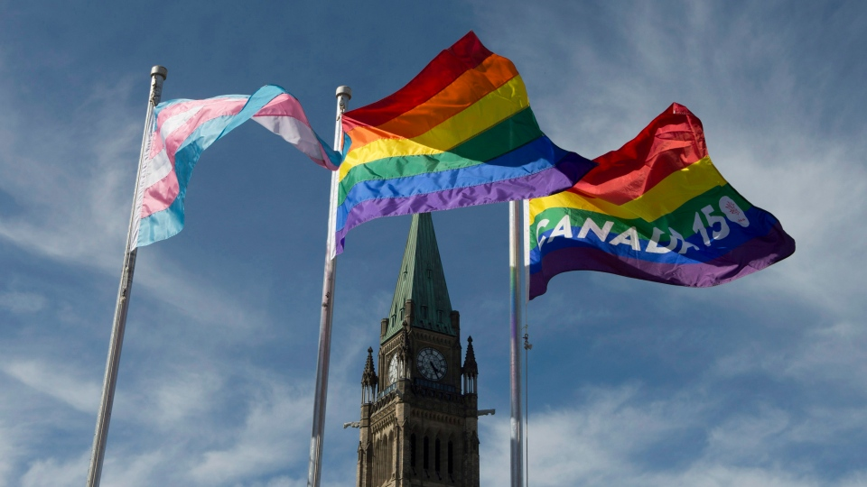 The pride and transgender flags fly on Parliament Hill following a ceremony with Prime Minister Justin Trudeau in Ottawa, Wednesday June 14, 2017. (Adrian Wyld / THE CANADIAN PRESS)