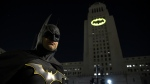 Tony Bradshaw, of Los Angeles, dressed as Batman, poses in front of a Bat-Signal projected onto City Hall during a tribute to 'Batman' star Adam West in Los Angeles on Thursday, June 15, 2017. (Chris Pizzello / Invision)