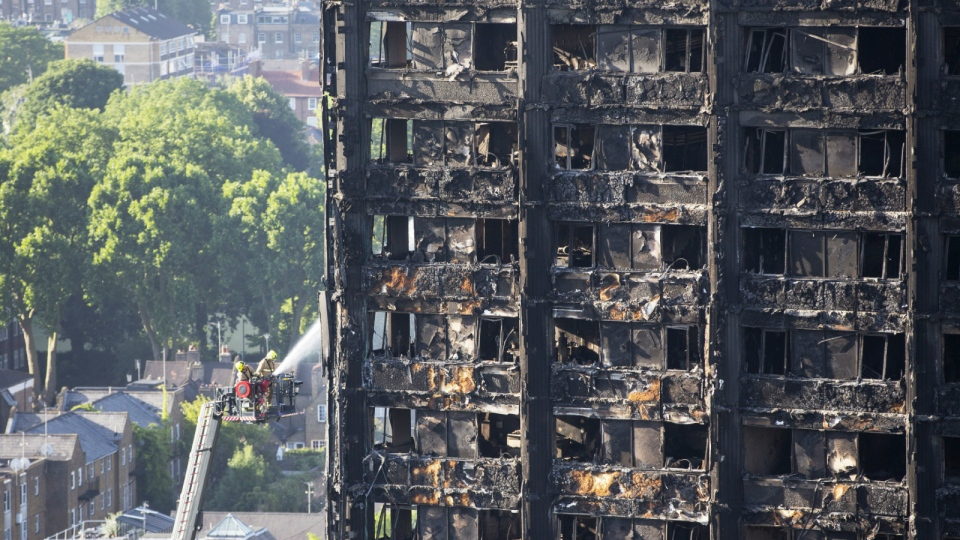 Firefighters on the ladder spray water on the fire-gutted Grenfell Tower in London on Friday, June 16, 2017. (Rick Findler / PA)