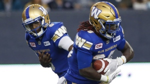 Winnipeg Blue Bombers quarterback Dominique Davis (6) hands off to Timothy Flanders (20) during the second half of CFL action against the Edmonton Eskimos in Winnipeg Thursday, June 15, 2017. THE CANADIAN PRESS/John Woods