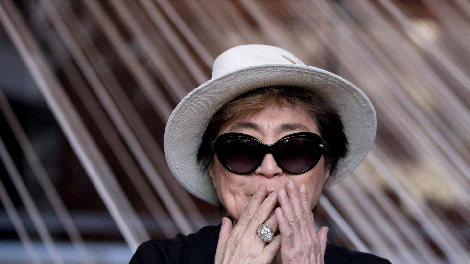 In this Tuesday, Feb. 2, 2016 photo, Yoko Ono blows a kiss as she poses for photographers in front of a work entitled, 'Morning Beams/River Bed,' at a press event to mark the opening of her exhibition, 'Land of Hope' at the Museum of Memory and Tolerance in Mexico City. (AP / Rebecca Blackwell)
