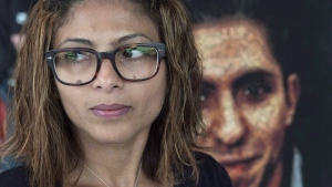 Ensaf Haidar, wife of Raif Badawi, stands next to a poster of a book of articles written by the imprisoned Saudi blogger, Tuesday, June 16, 2015 in Montreal. (Paul Chiasson/The Canadian Press)