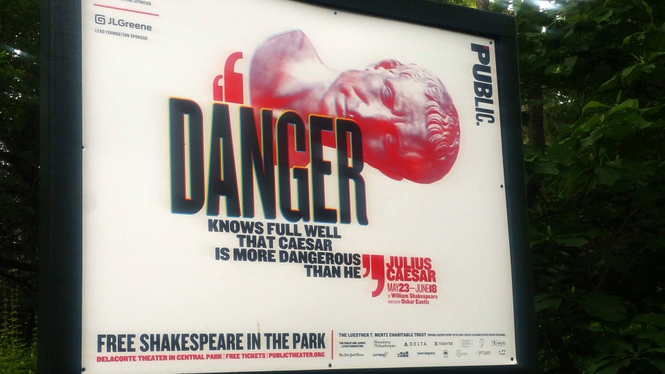 "In this June 7, 2017 photo, ""Danger knows full well that Caesar is more dangerous than he,"" reads a sign promoting The Public Theater's production of Julius Caesar in New York's Central Park. Police say they arrested a woman during the Friday, June 16, performance, and charged her with criminal trespass and disorderly conduct for getting up on stage and disrupting the play. (AP Photo / Verena Dobnik)"