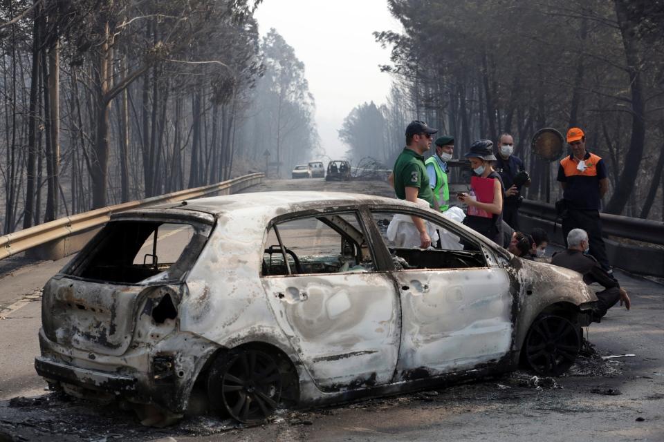 Police investigators stand by a burnt car on the road between Castanheira de Pera and Figueiro dos Vinhos, central Portugal, Sunday, June 18 2017. (AP / Armando Franca),