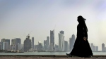 In this May 14, 2010 file photo, a Qatari woman walks in front of the city skyline in Doha, Qatar. (AP Photo/Kamran Jebreili, File)