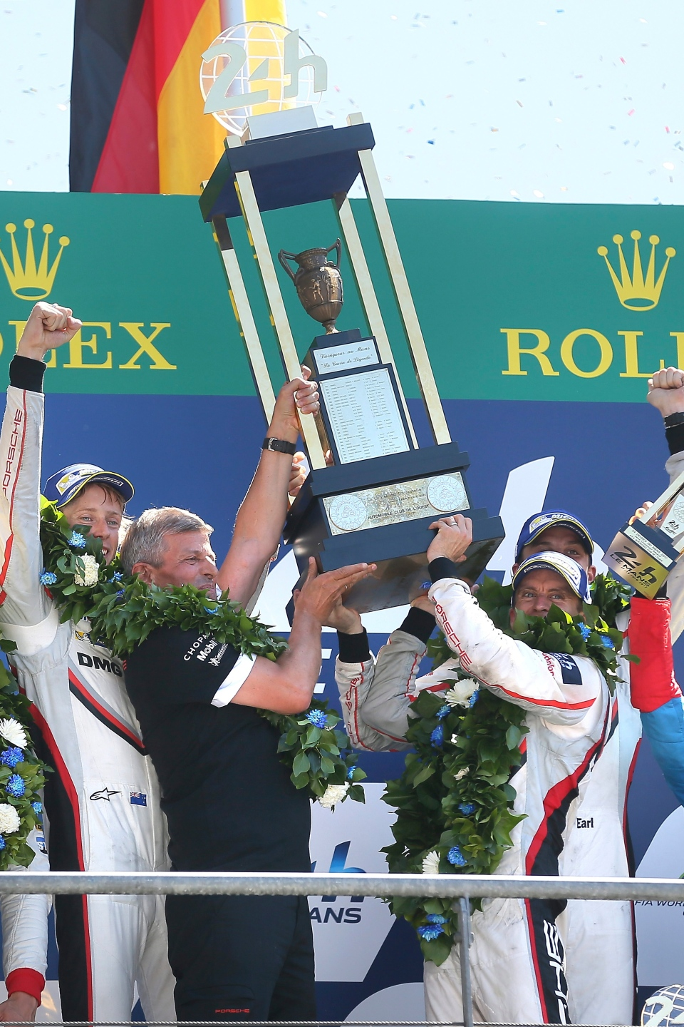 Driver Brendon Hartley of New Zealand, Fritz Enzinger, president of Porsche Team, Earl Bamber of New Zealand and German driver Timo Bernhard hold the Trophy during the podium ceremony of the 85th 24-hour Le Mans endurance race, in Le Mans, western France, Sunday, June 18, 2017. (David Vincent/AP Photo)
