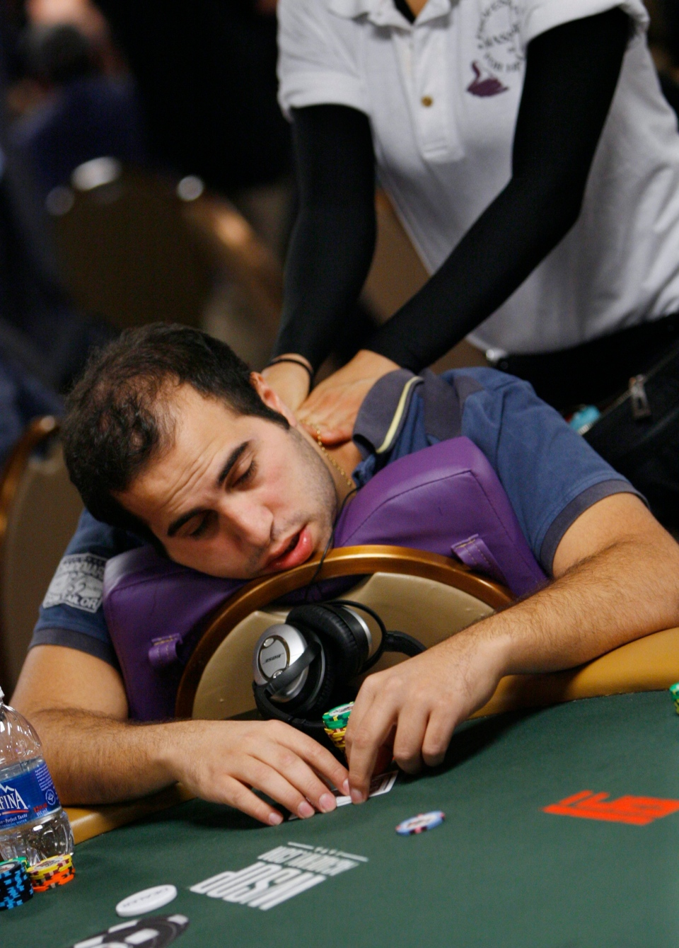 Nicholas Shouiti of Lebanon gets a massage while playing a hand in the first round on opening day of the World Series of Poker in Las Vegas on Monday, July 5, 2010. (Laura Rauch/AP Photo)