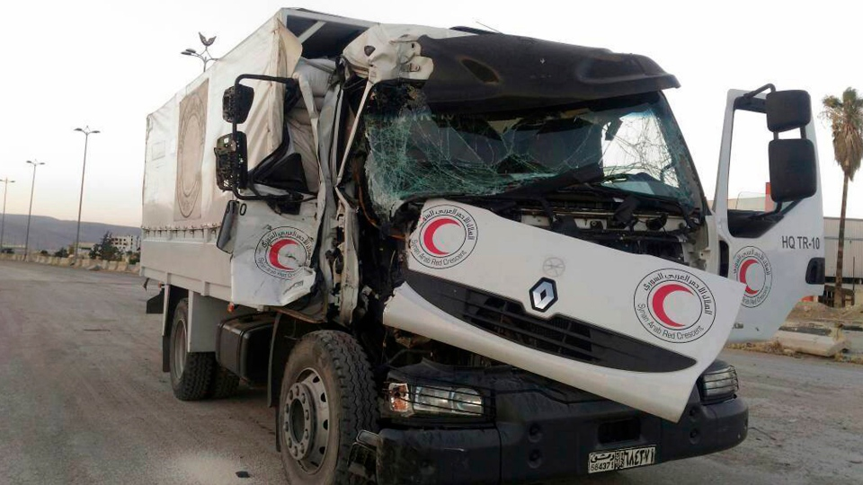 This image provided by the Syrian Arab Red Crescent shows the aftermath of an attack on a humanitarian aid convoy that came under fire shortly before dark Saturday, June 17, 2017, outside Damascus, Syria. The International Committee of the Red Cross says the humanitarian aid convoy to a besieged opposition area outside Syria's capital has come under attack, wounding a driver and thwarting the first such mission to the area in eight months. (Syrian Arab Red Crescent via AP)