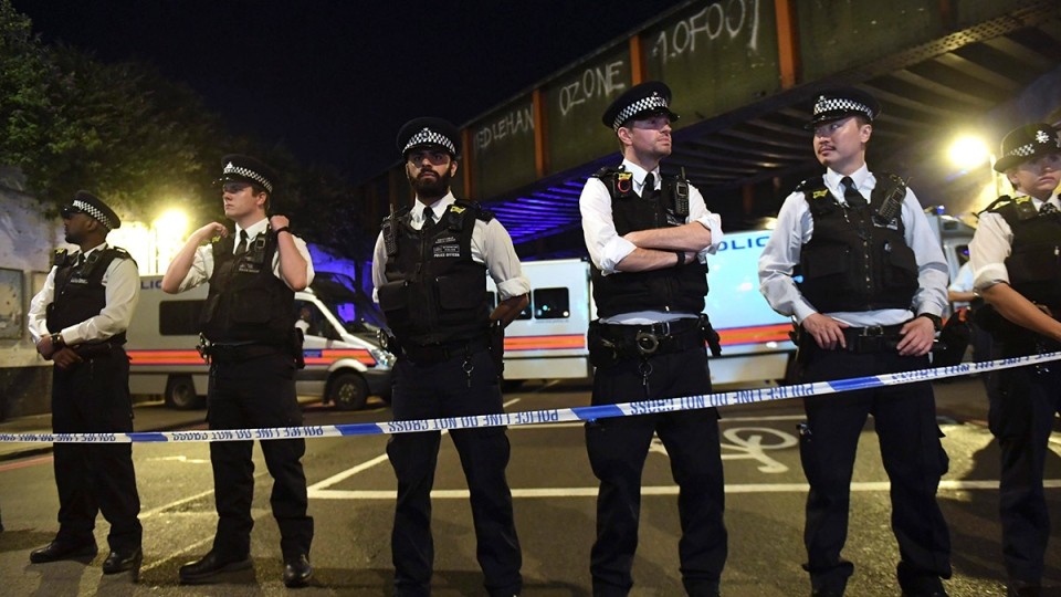 Police officers man a cordon near the Seven Sisters Road at Finsbury Park where a vehicle struck pedestrians in London Monday, June 19, 2017. (Yui Mok / PA)