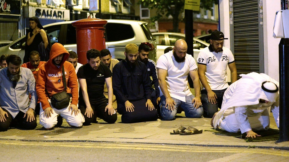 Local people observe prayers at Finsbury Park where a vehicle struck pedestrians in London Monday, June 19, 2017. (Yui Mok / PA)