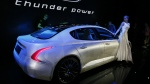 A model poses near a sports sedan from Thunder Power during a brand event held in Beijing on Wednesday, May 24, 2017. (AP / Ng Han Guan)