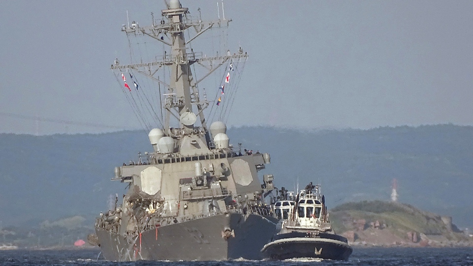 USS Fitzgerald is towed by a tugboat in the waters near the U.S. Naval base in Yokosuka, southwest of Tokyo, on June 17, 2017. (Eugene Hoshiko / AP)