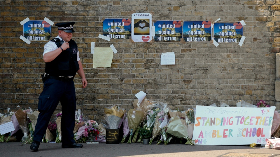 A policeman stands near floral tributes left after an incident, close to Finsbury Park Tube Station, in north London, on June 19, 2017. (Alastair Grant / AP)