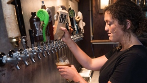 Bartender Jen Atkinson pours a Maybee craft beer at James Joyce Pub in the Crowne Plaza Hotel in Fredericton, N.B., on Friday, June 16, 2017. (Stephen MacGillivray/The Canadian Press)