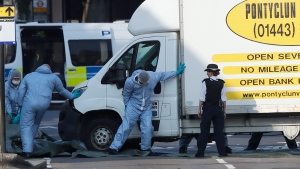 Forensic officers move the van at Finsbury Park in north London, where a vehicle struck pedestrians in north London Monday, June 19, 2017. (AP Photo/Frank Augstein)