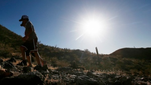 FILE - In this June 15, 2017 file photo, hikers brave the afternoon sun as the temperatures hit 110-degrees in Phoenix. (AP Photo/Ross D. Franklin, File)