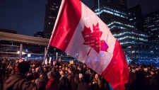 A man waves a Canadian flag during a rally against Islamophobia in Vancouver, B.C., on Saturday February 4, 2017. THE CANADIAN PRESS/Ben Nelms