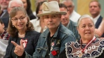 Tragically Hip singer Good Downie raises his arm in response to a speaker as he sits with Sylvia Maracle (right) and Jacqueline Guest(left) during an awards ceremony Monday, June 19, 2017 in Ottawa. Downie and Guest were invested into the Order of Canada, and Maracle was invested as an Officer of the Order.THE CANADIAN PRESS/Adrian Wyld