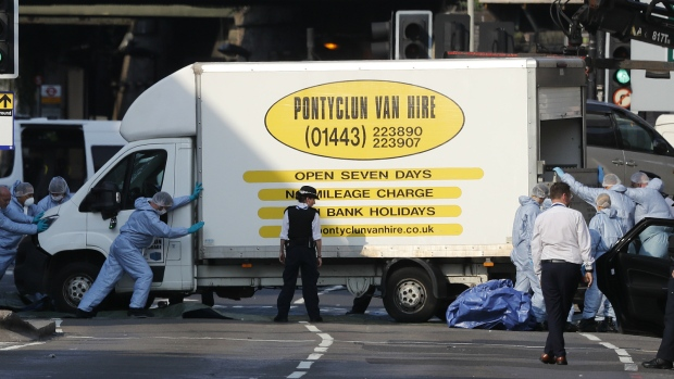 Forensic officers move the van at Finsbury Park in north London, where a vehicle struck pedestrians in north London on Monday, June 19, 2017. (AP / Frank Augstein)