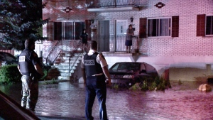 Police keep watch as water from a broken water main floods Belcourt St. in Longueuil on June 20, 2017 (CTV Montreal/Cosmo Santamaria)