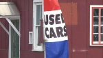 A used car flag flaps in the wind outside 'Quality Motors' on Cyrville Road in Ottawa.