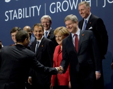 U.S. President Barack Obama approaches Prime Minister Stephen Harper to shake hands as leaders look on during the second 'family photo' at the G20 in London, England, Thursday, April 2, 2009. The family photo was restaged after Harper missed the initial photo op. (Adrian Wyld / THE CANADIAN PRESS)