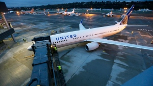 In this file image, workers walk up the steps of a jetway of a new Boeing 737-900ER airplane being delivered to United Airlines as it sits parked in front of Boeing's expanded 737 delivery centre, Monday, Oct. 19, 2015, at Boeing Field in Seattle. (AP / Ted S. Warren)
