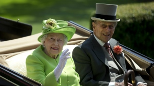 Queen Elizabeth II, left, waves to the crowd with Prince Philip at right, as they arrive by open carriage to the parade ring on the first day of the Royal Ascot horse race meeting in Ascot, England on Tuesday, June 20, 2017. (AP / Alastair Grant)