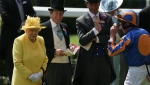 Queen Elizabeth II speaks with jockey Ryan Moore, right, and racing manager John Warren, second left, after arriving in the parade ring on the second day of the Royal Ascot horse race meeting in Ascot, England, Wednesday, June 21, 2017. (AP Photo/Tim Ireland)