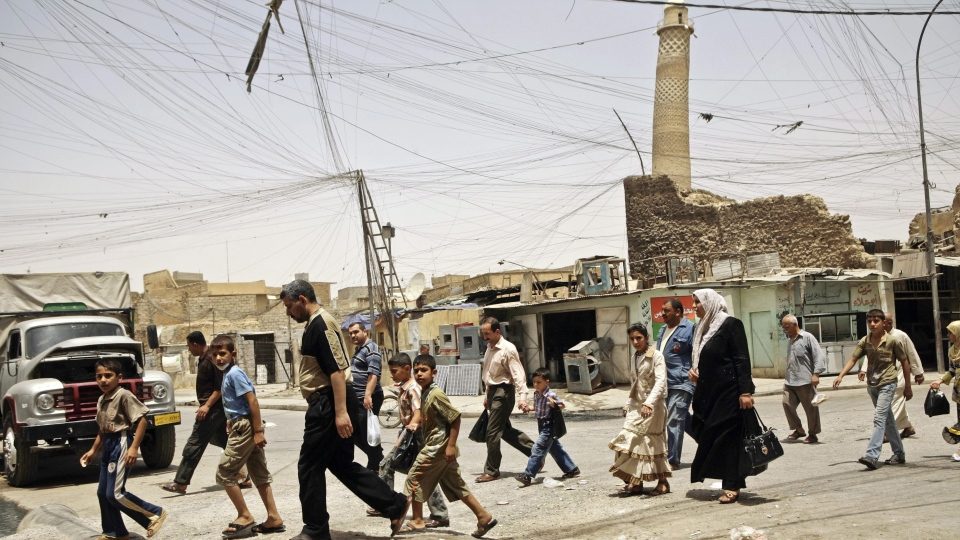 In this Monday, June 8, 2009 file photo, residents walk past the crooked minaret in a busy market area in Mosul, Iraq. The Iraq ministry of defense says Islamic State militants destroyed the al-Nuri mosque in Mosul and the adjacent iconic leaning minaret when fighters detonated explosives inside the structures late Wednesday night on June 21, 2017. (AP Photo / Maya Alleruzzo, File)